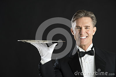 Portrait Of Happy Waiter Wearing Tuxedo Carrying Serving Tray