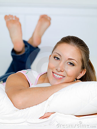 Portrait of happy woman lies on a pillow
