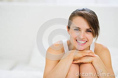 Portrait of happy woman sitting on bed