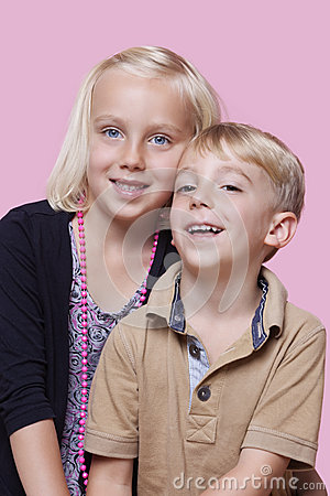 Portrait of happy young boy with sister over pink background