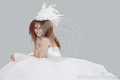 Portrait of happy young bride sitting over gray background