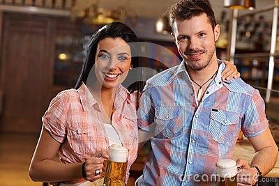 Portrait of happy young couple in pub
