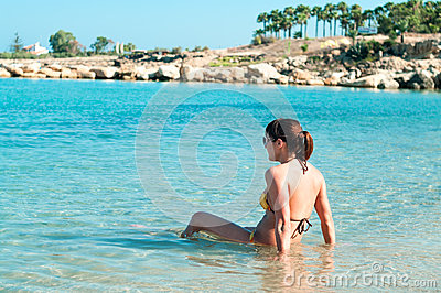 Young woman in bikini sitting on shoreline