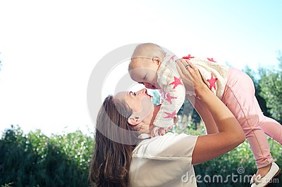 Portrait of a happy young mother lifting cute baby outdoors