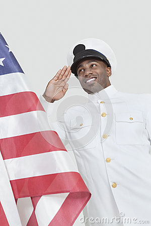 Portrait of a happy young US Navy officer saluting American flag over gray background