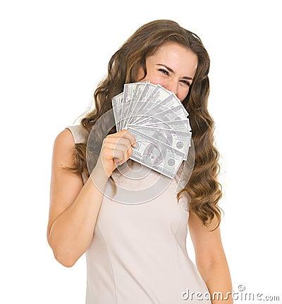 Portrait of woman hiding behind fan of dollars