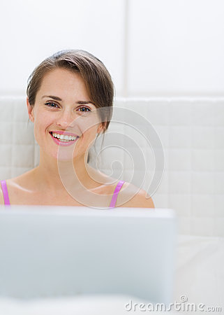 Portrait of happy young woman with laptop in bed