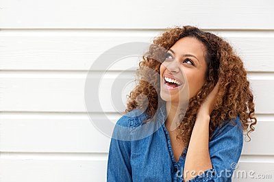 Portrait of a happy young woman laughing outdoors with hand in hair