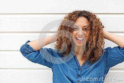 Portrait of a happy young woman smiling with hands in hair