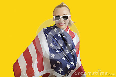 Portrait of happy young woman wrapped in American flag over yellow background