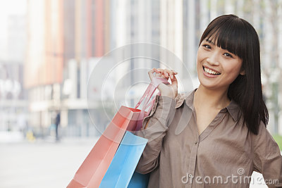 Portrait of happy, young women going shopping and holding colorful shopping bags on the street in Beijing, China