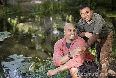 Portrait Hispanic father and son outdoors by pond