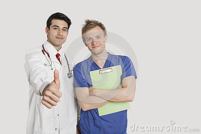 Portrait of an Indian doctor gesturing thumbs up while standing with male nurse over light gray background