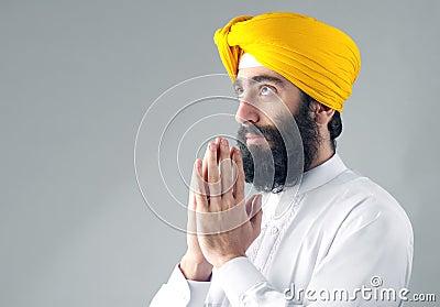 Portrait of Indian sikh man with a bushy beard praying