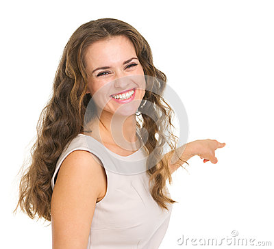 Portrait of interested young woman pointing back