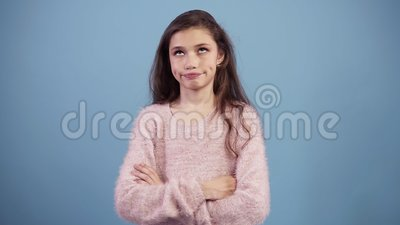 Portrait of irritated long haired teen girl rolling her eyes while being fed up or bored, isolated over blue background. Concept of emotions stock video