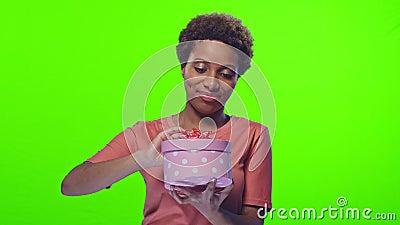 Portrait joyeuse jeune femme afro-américaine dansant joyeusement avec une boîte cadeau banque de vidéos
