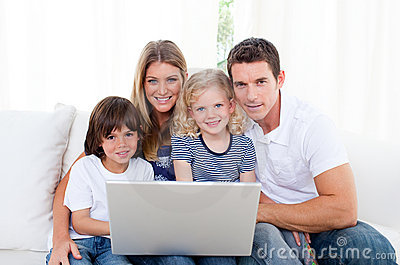 Portrait of a joyful family using a laptop