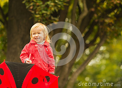 Portrait of laughing baby with red umbrella