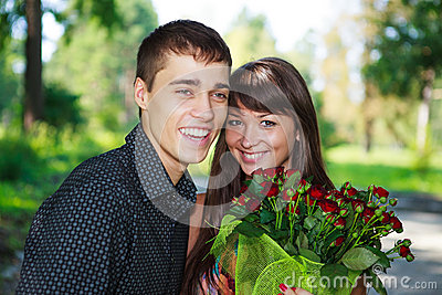Portrait laughing lovers young couple with a bouquet of red rose