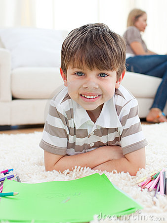 Portrait of little boy drawing lying on the floor