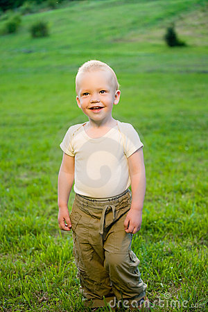 Portrait of little boy on green grass field