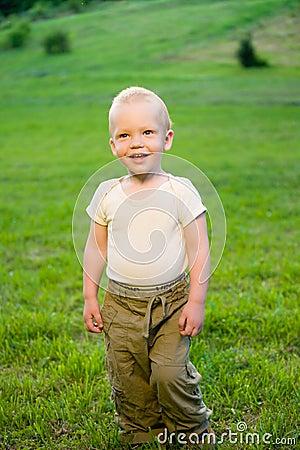 Portrait of little boy on green grass field