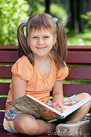Portrait of little cute smiling girl with book