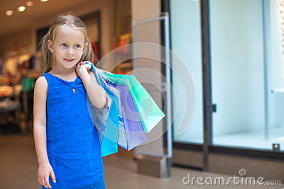Portrait of little fashion girl holding shopping
