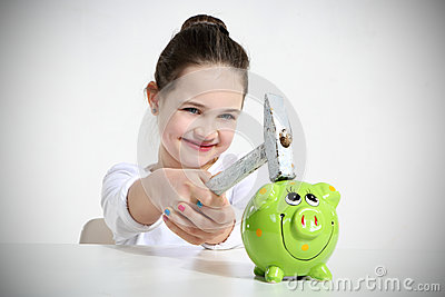 Portrait of little girl breaking piggy bank