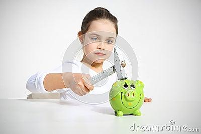 Portrait of little girl breaking piggy bank