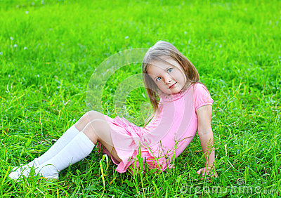 Portrait Of Little Girl Child Sitting On The Grass Stock