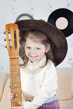 Portrait of the little girl with a guitar in hands