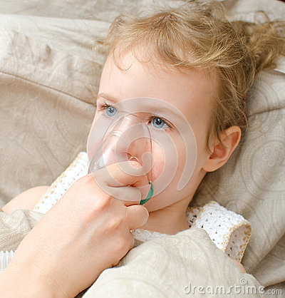 Portrait of little girl lying in bed with inhalator mask