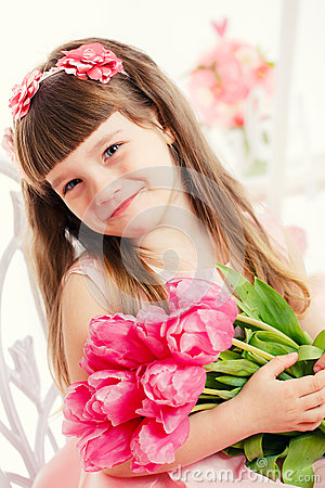 Portrait of a little girl, pink tulips in hands