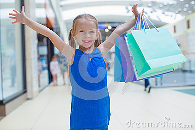 Portrait of little happy girl holding shopping