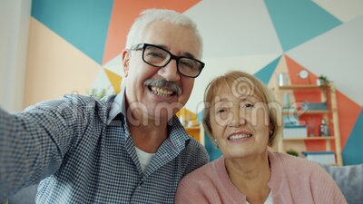 Portrait of lovely old couple enjoying online video call showing thumbs-up talking. Laughing looking at camera. Communication and technology concept stock video footage