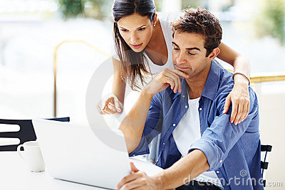 Portrait of lovely young couple working on laptop