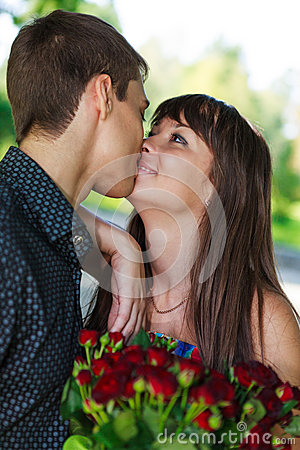 Portrait lovers kissing young couple with a bouquet of red roses