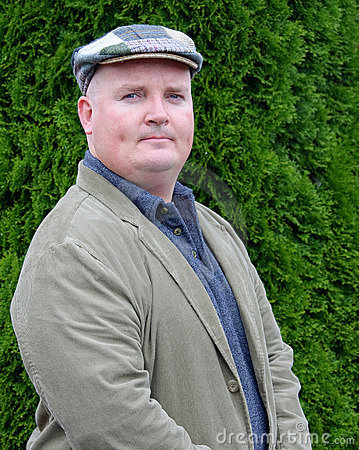 Portrait of a male outside in jacket and tweed hat