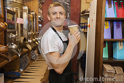 Portrait of male salesperson holding disposable coffee cup in store