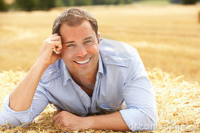 Portrait Of Man Laying In Summer Harvested Field