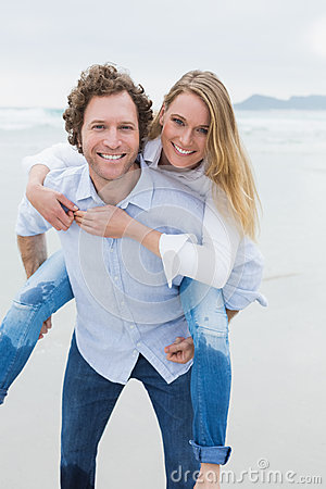 Portrait of a man piggybacking woman at beach