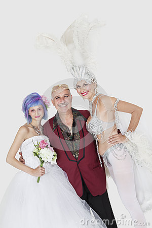Portrait of man with senior showgirl and daughter in wedding dress over gray background