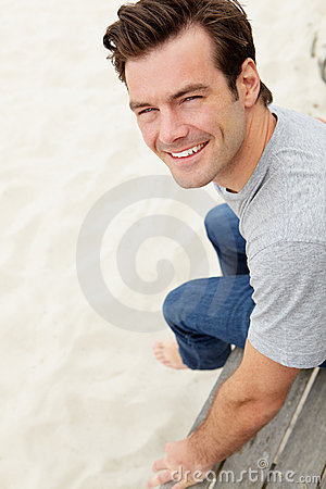 Portrait of man sitting by beach