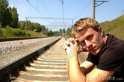 Portrait of the man sitting on the railway in a br