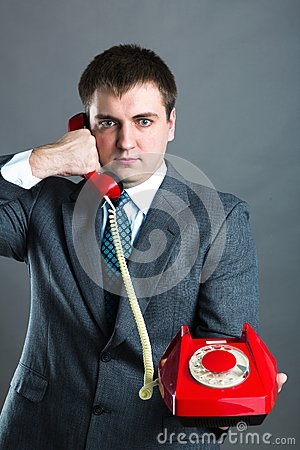 Portrait of a man speaking phone isolated on gray