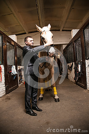 Portrait of man in suit stroking brown horse