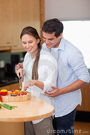 Portrait of a man teaching how to cook to his wife