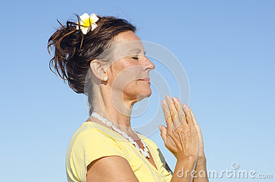 Portrait meditating woman sky background